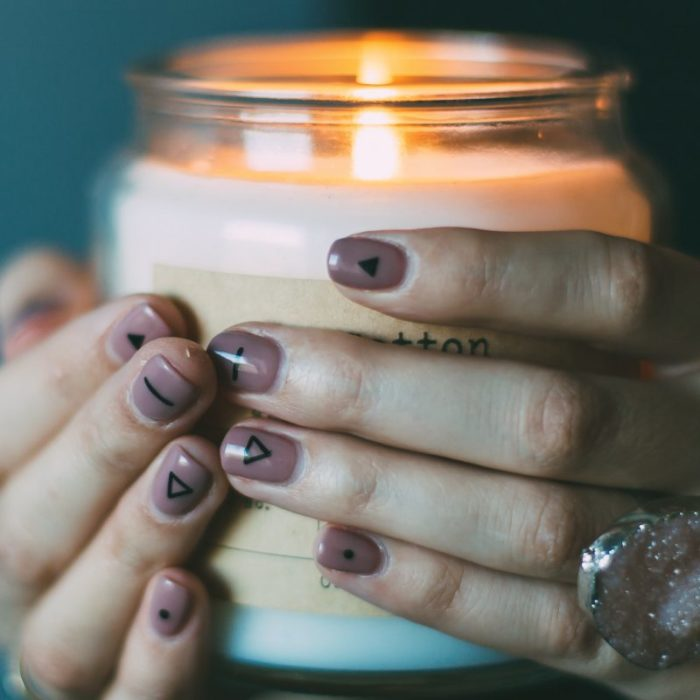 hand holding lit candle with nail art