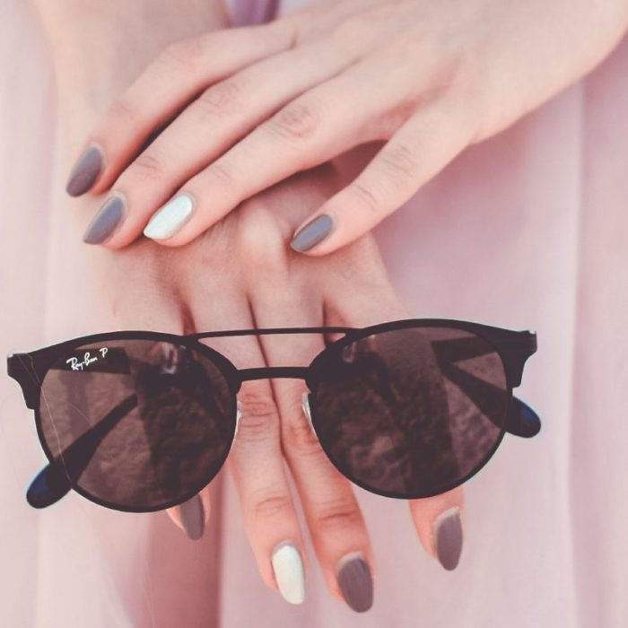colored nails holding raybans